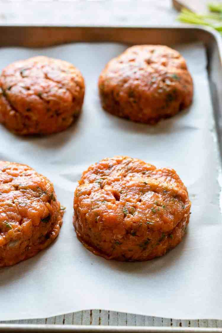 Thai Salmon Burger patties on a parchment-lined baking sheet.