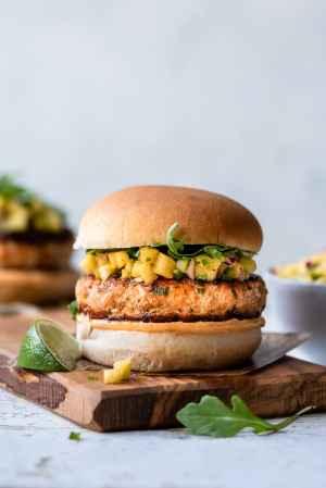 Thai Salmon Burger served on a bun with sriracha aioli and pineapple salsa on a wooden board.