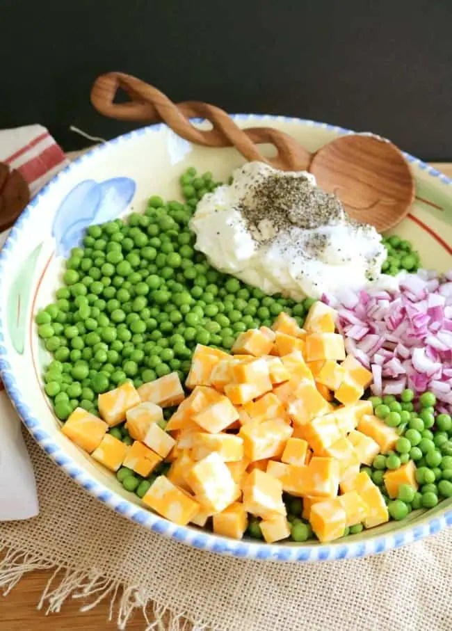 a large serving bowl filled with ingredients for English pea Salad: peas, cheese, red onions, mayonnaise, herbs and seasonings.