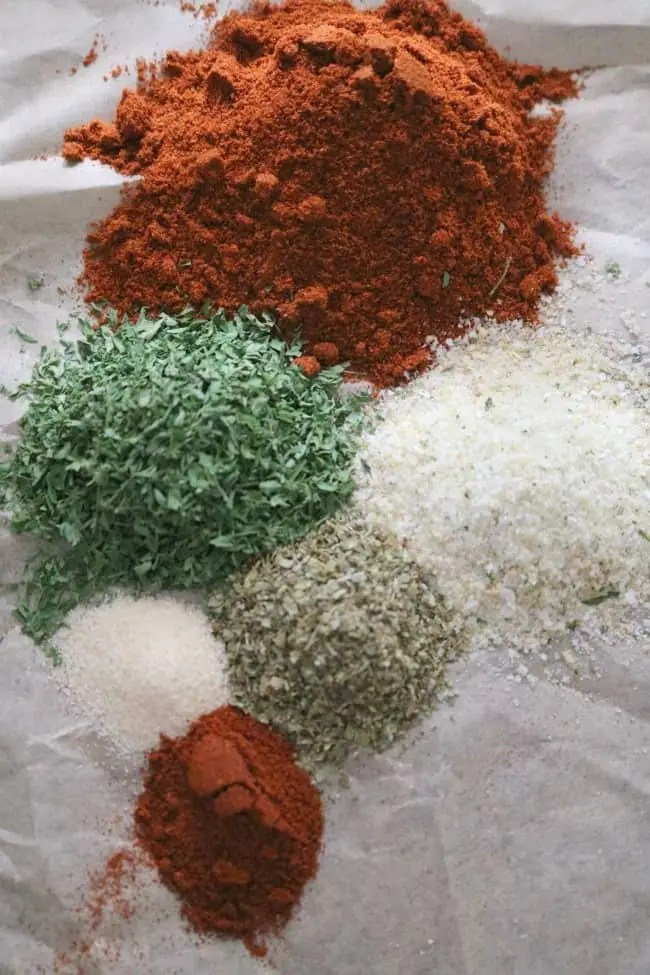 an image of herbs and spices on a sheet of parchment ready to be added to the ground pork for making homemade linguica sausage