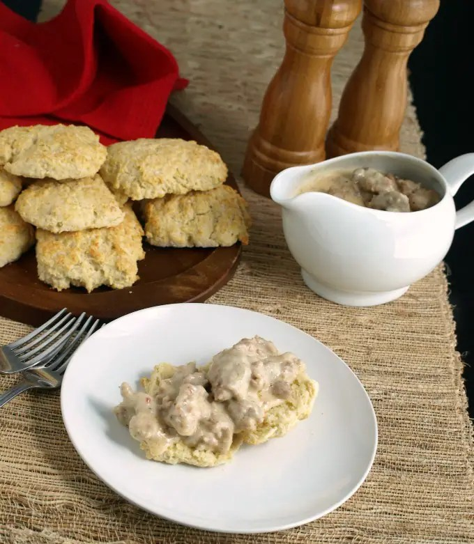 A plate of Biscuits and gravy on a woven mat.