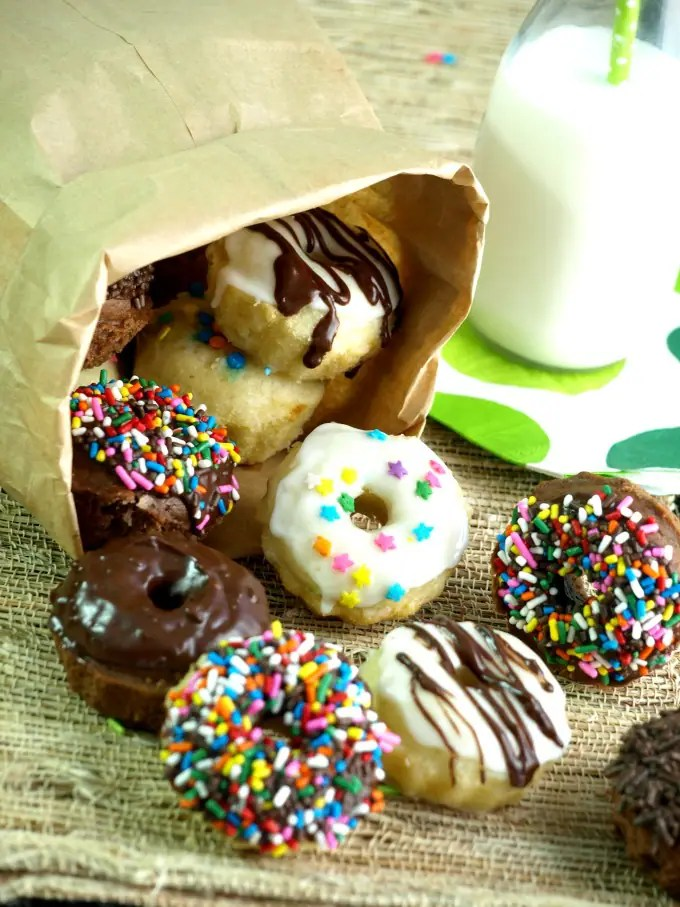 A paper bag with mini baked doughnuts spilling out of it next to a glass of milk.