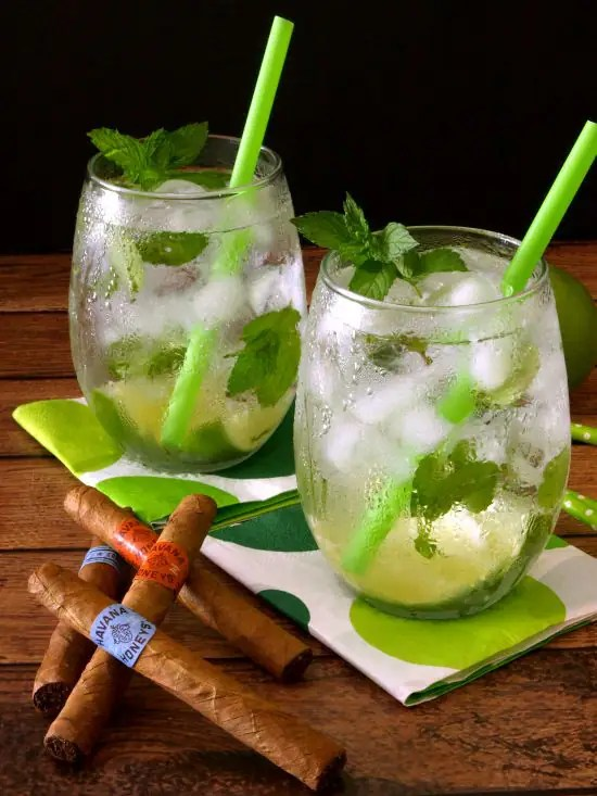 Classic mint mojitos against a black background with Havana cigars.