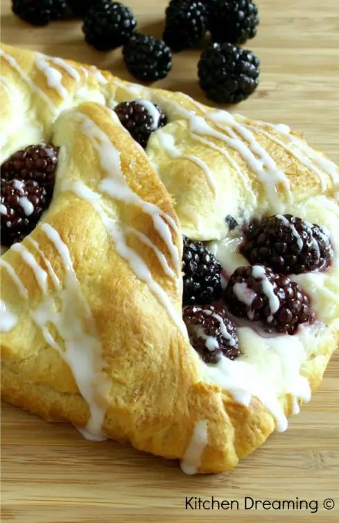 A cheese danish filled with cream cheese and fresh blackberries on a cutting board surrended by more fresh berries.