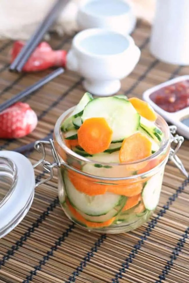 A jar of pickled vegetables on a dinner table