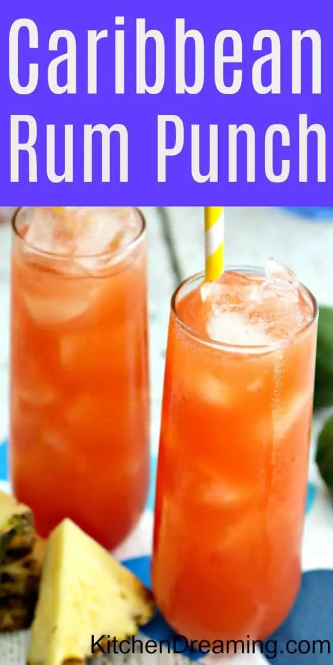 Two tall galsses of Caribbean rum punch with yellow straws and slices of fresh pineapple on a blue polka dotted napkin.