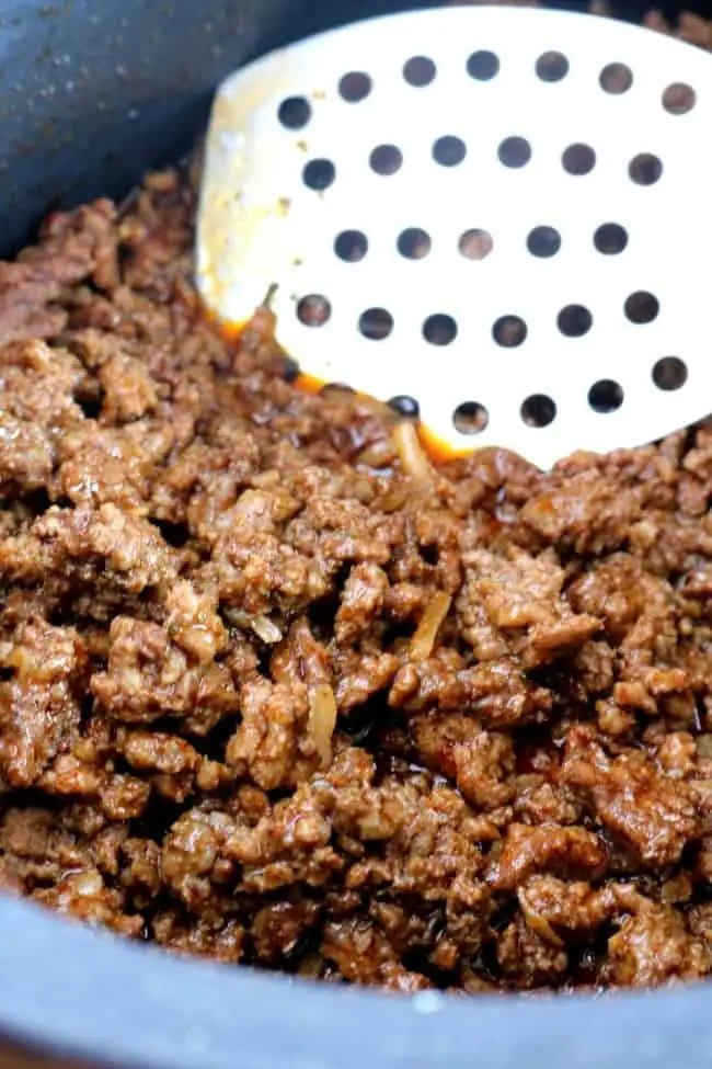 Ground Beef seasoned with taco seasoning in the slow cooker insert with a slotted spoon.