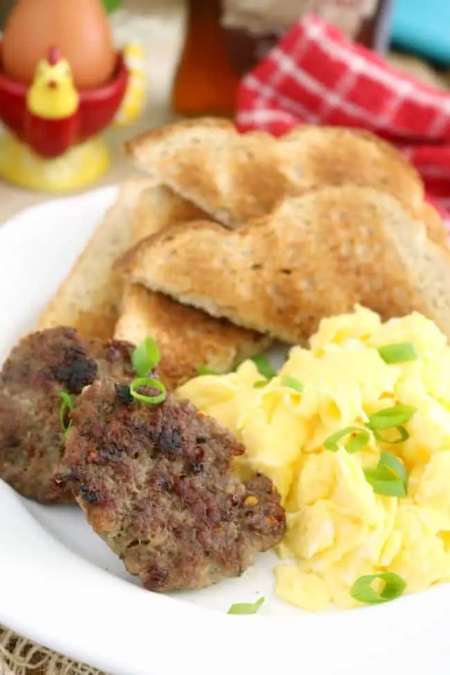 a plate of scrambled eggs, two slices buttered toast, and two homemade breakfast sausage patties