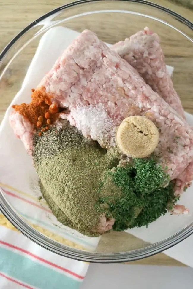 an in-process image of a bowl of ground pork with herbs and pork ready to make homemade breakfast sausage