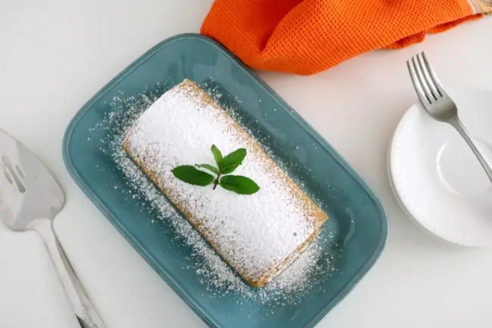 An overhead image of a pumkin cake roll on a blue plate with a cake server with an orange tea towel.