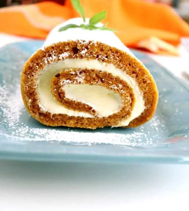 A shot of an end of a pumpkin cake roll showling the swirl of cake and cream.