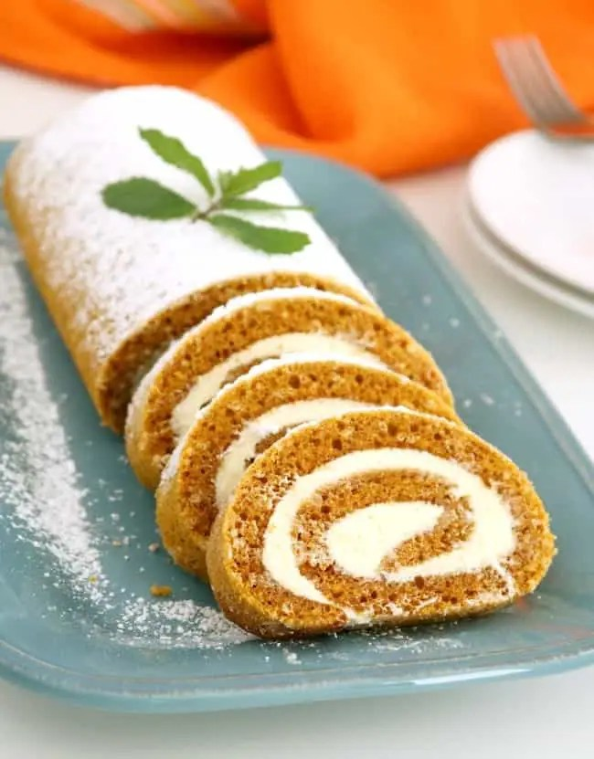An image of a plate of pumpkin cake roll that is sliced to serve. It is garnished with a sprig of holly.