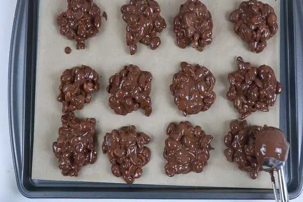 A sheetpan lined with parchent paper that has portioned choclate peanut clusters. The last porting is being added to the bottom right corned of the pan with a small scoop.