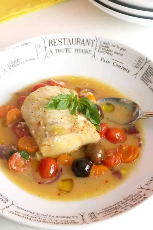 a plate of poached cod with saffron and tomatoes