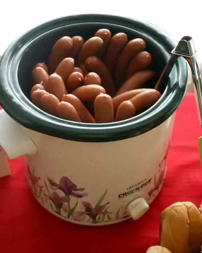 The slow cooker is a great way to keep an abundance of hot dogs hot over a long period of time. Grilled or not, just pile them into the slow cooker and set it on low. This allows you to grill them ahead of time. Perhaps your summer plans got rained out and you need a quick and easy way to move the party indoors. This idea works great for game days, tailgating (with a plug adapter), and kids birthday parties, too.