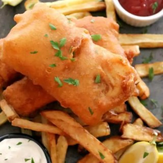 Fried Fish and french fries on a dark slate tile.