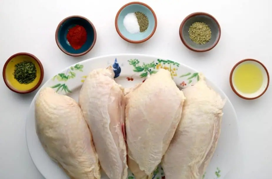 A table containing the ingredients for juicy oven baked chicken breasts: bone-in chicken breasts, salt, pepper, olive oil, paprika, dried rosemary, and dried parsley.