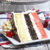 Banana Split Cake with layers of strawberry, vanilla and chocolate cake that looks like real ice cream is dripping on top. Yum!