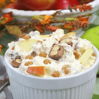 Twix Apple Dessert Salad recipe prepared and in a white ramekin sitting on a green plaid cloth