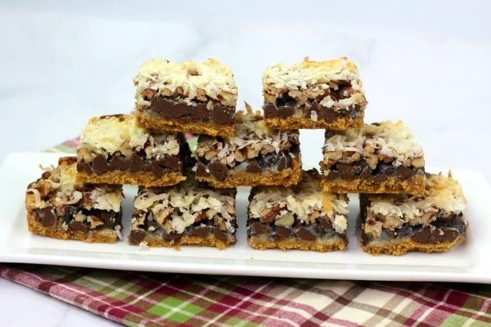 Hello Dolly Cookie Bars in a pyramid stack on a white serving tray on red plaid cloth