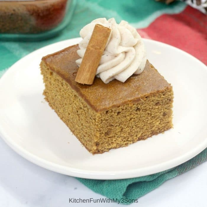 Single slice of old fashioned gingerbread cake on a white plate with frosting