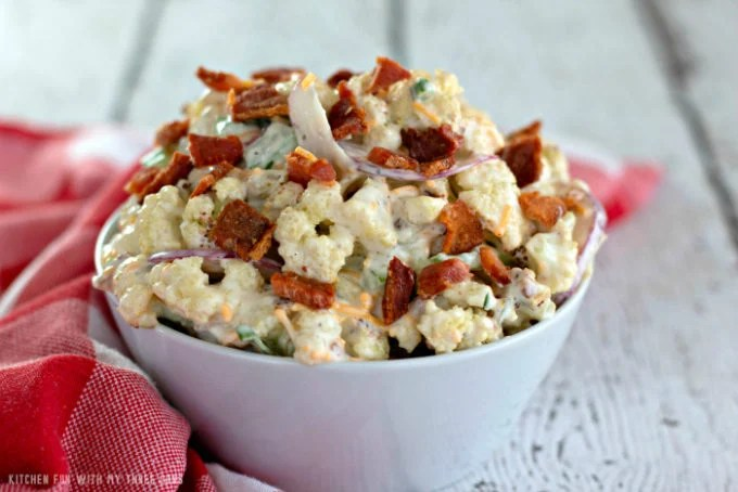 Low Carb Cauliflower Salad in a white bowl on a rustic white table with a red and white check napkin