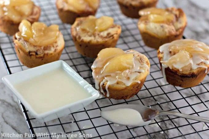 drizzling frosting over cinnamon rolls filled with apple pie filling