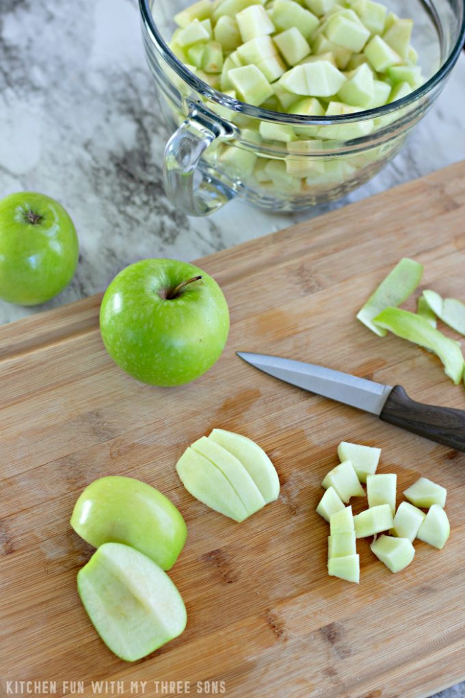cutting Granny Smith apples on a bamboo cutting board to make homemade apple pie