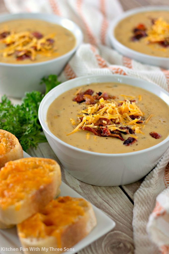 three white bowls filled with Beer Cheese Soup with Garlic Cheese Toast
