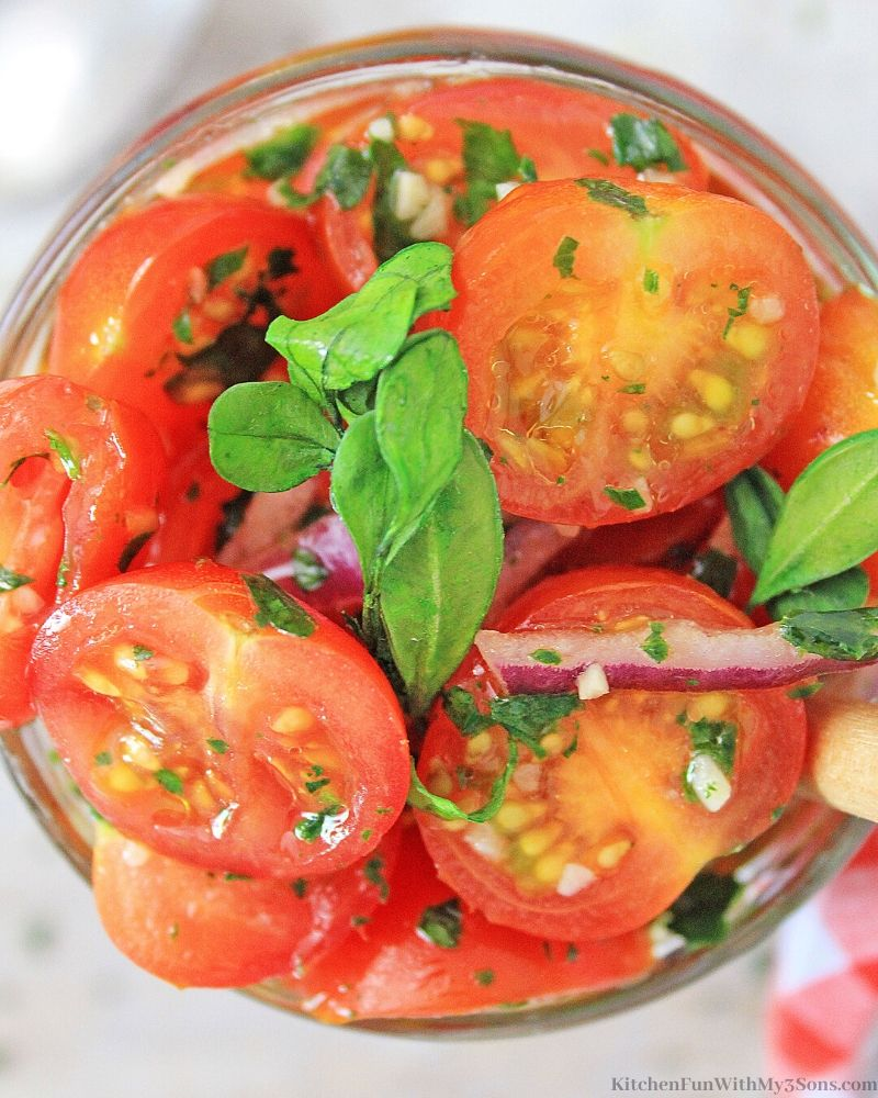 overhead picture of marinated tomatoes in a jar