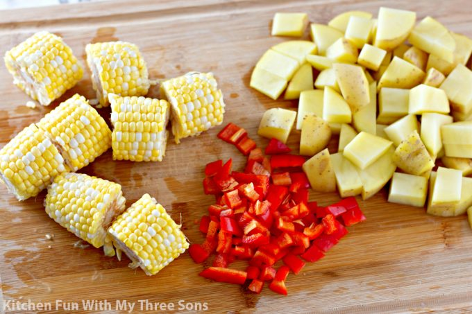 chopping potatoes, peppers, and corn on the cob