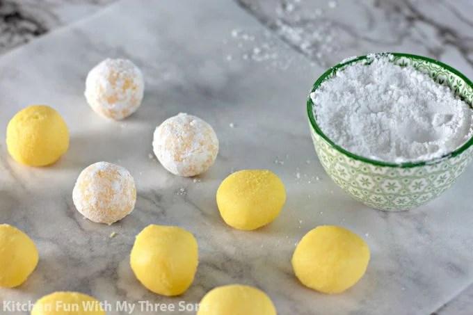rolling lemon candies in powdered sugar