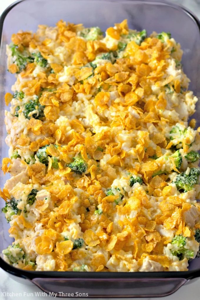 chicken and rice with cheese and broccoli in a glass baking dish topped with buttered Corn Flakes