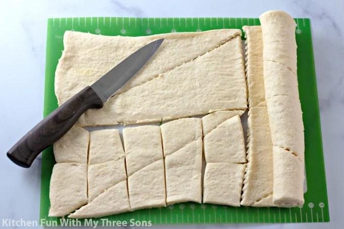 cutting crescent roll dough on a cutting mat