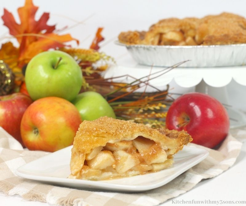 Bourbon Apple Pie Recipe with apples, twigs and leaves behind the plate.