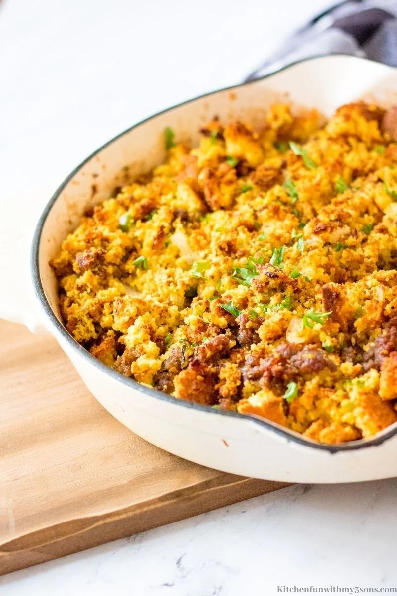 Best Ever Sausage Cornbread Stuffing finished and in a white skillet.