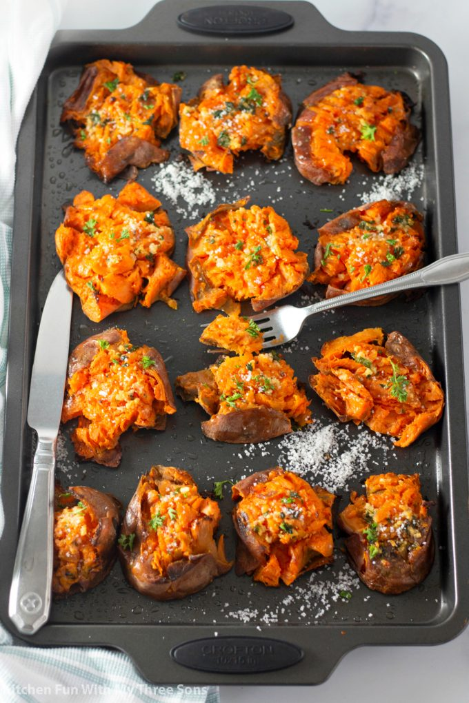 Garlic Butter Smashed Sweet Potatoes on a cookie sheet with a knife and fork