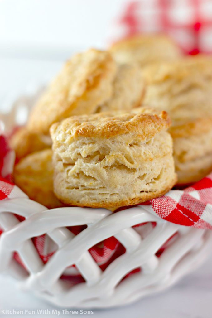 Honey Butter Biscuits in a white basket with a red checkered napkin