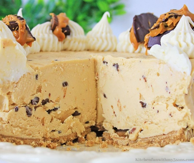 The whole Peanut Butter Chocolate Chip Cheesecake with a slice cut out of it.