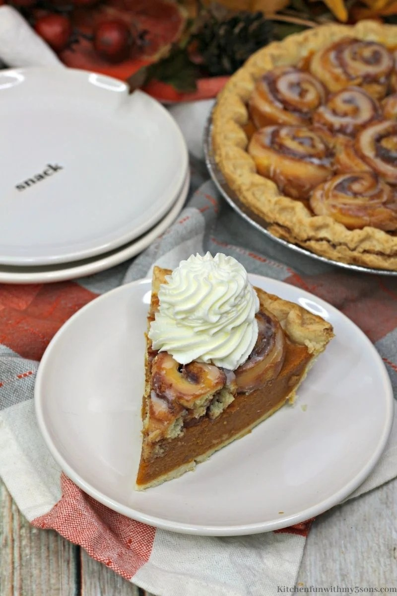 Pumpkin Cinnamon Roll Pie topped with whipped cream.