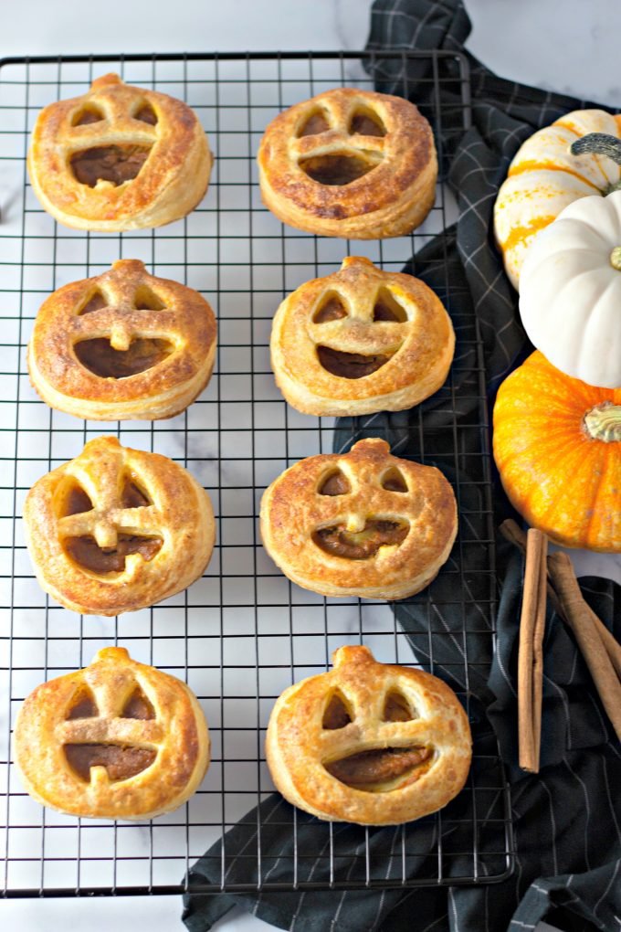 Easy Pumpkin Hand Pies on a wire cooling rack with a black towel and pumpkins