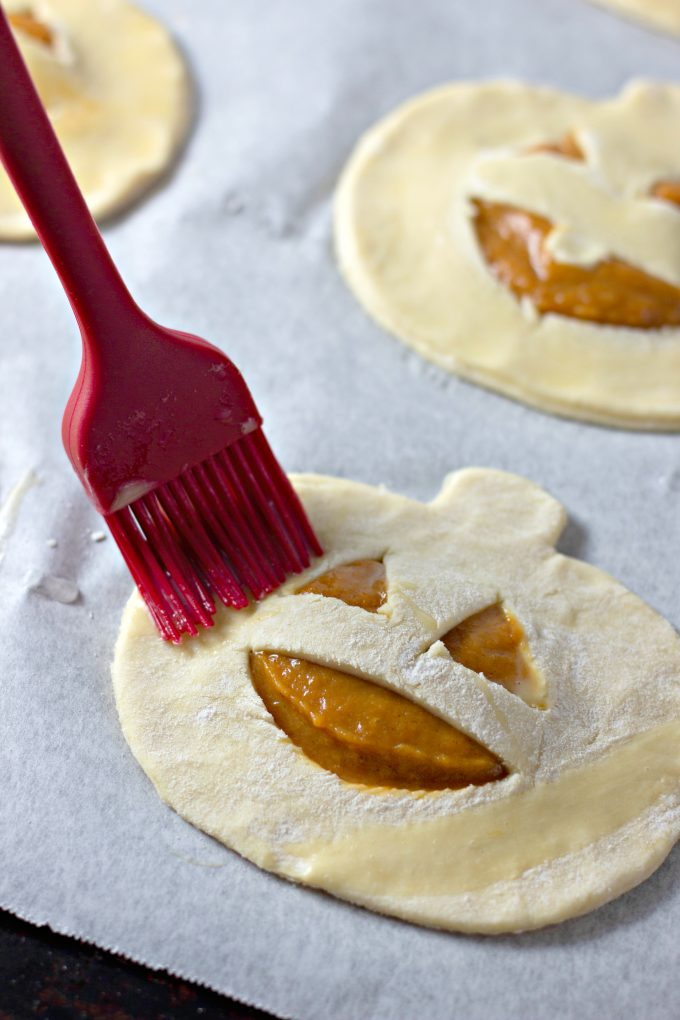 brushing the pies with egg wash