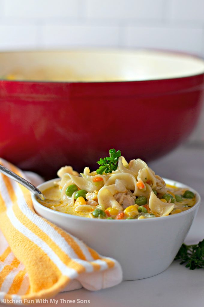 Chicken Pot Pie Noodles in a white bowl with fresh parsley