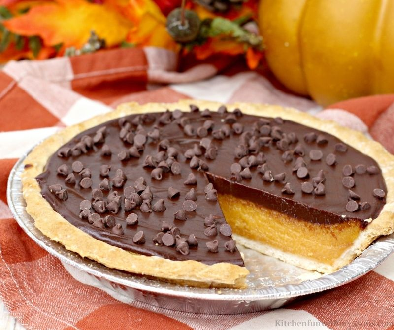Chocolate Sweet Potato pie on a white and red cloth with Fall decorations behind it.