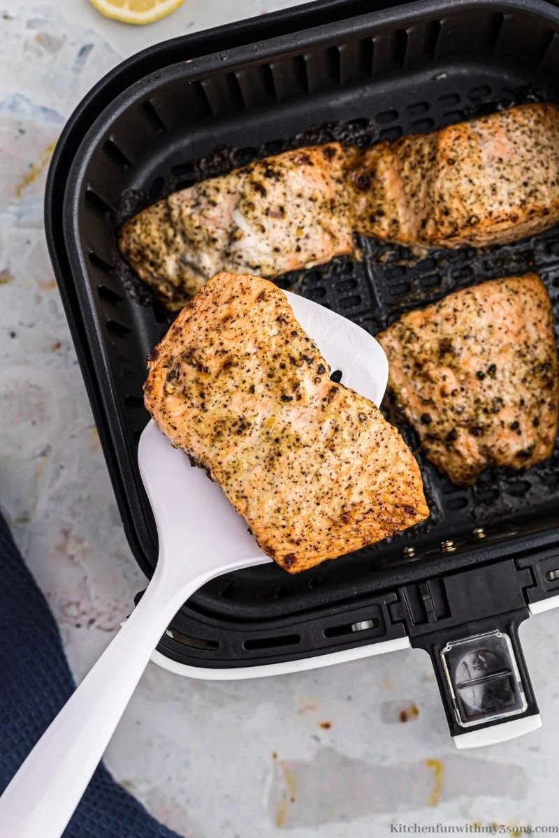 Your finished salmon being taken out of the air fryer.
