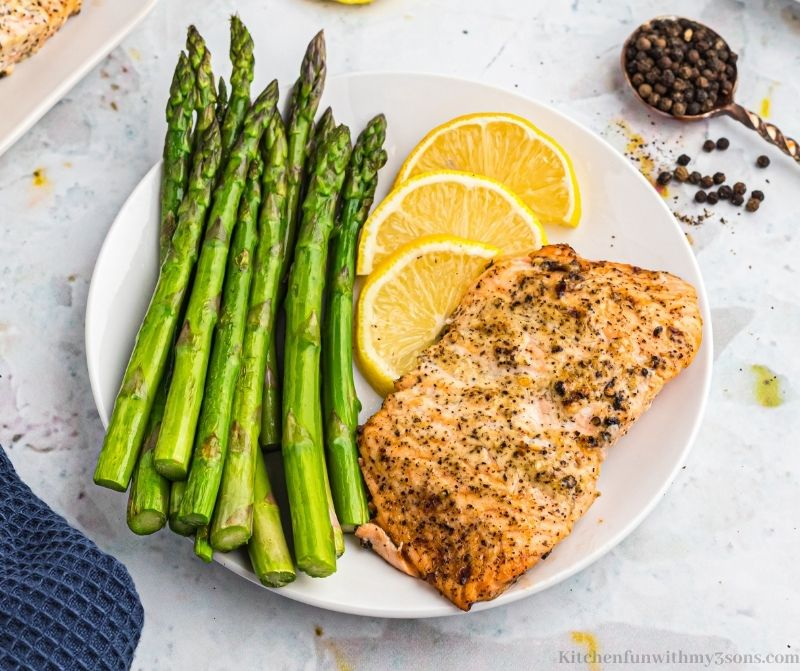 Lemon Pepper Air Fryer Salmon on a serving plate with a side of asparagus.