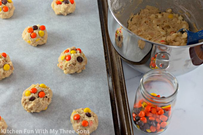 pressing Reese's Pieces onto the cookie dough balls