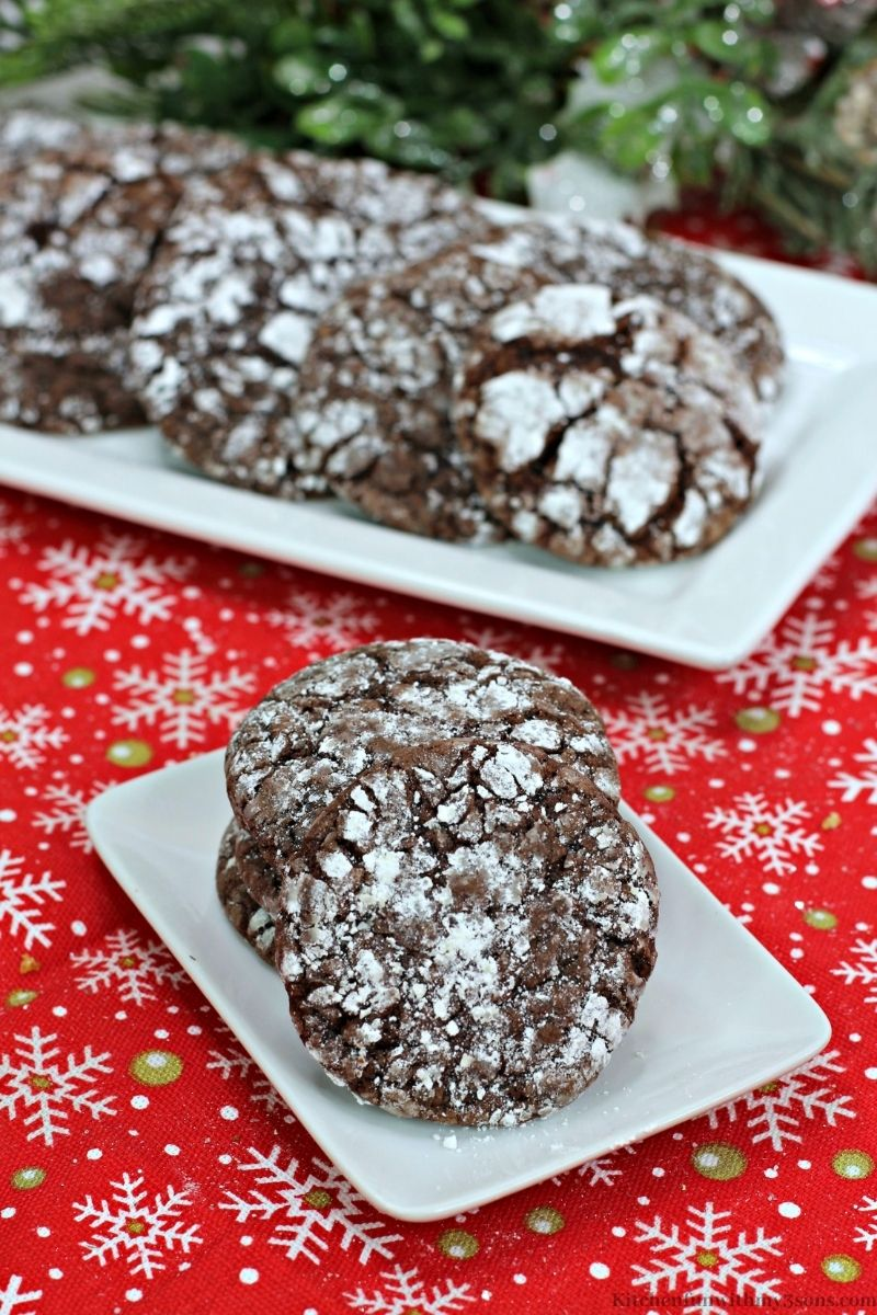 Chocolate Rum Crinkle Cookies on a plate with more behind them on a serving platter.
