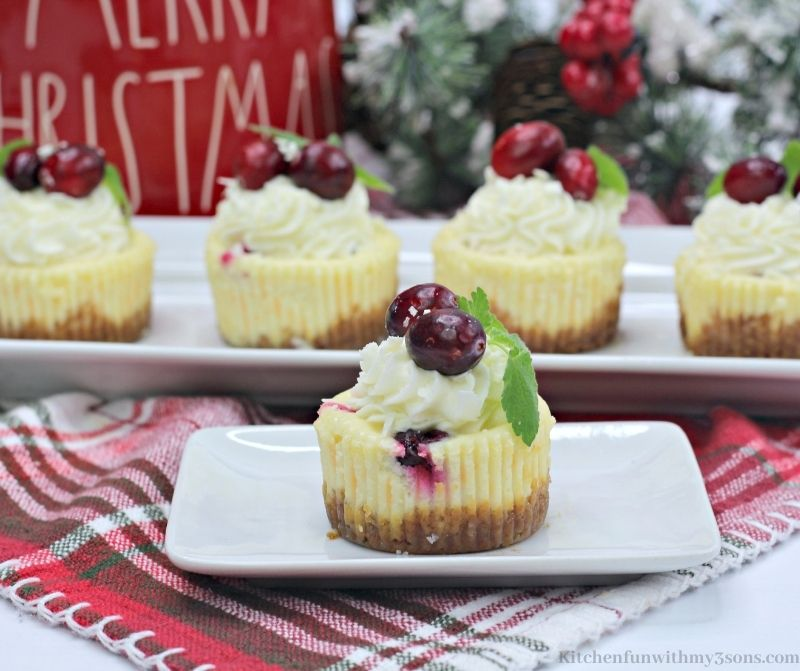 Mini White Chocolate Cranberry Cheesecake with Christmas decorations behind it.