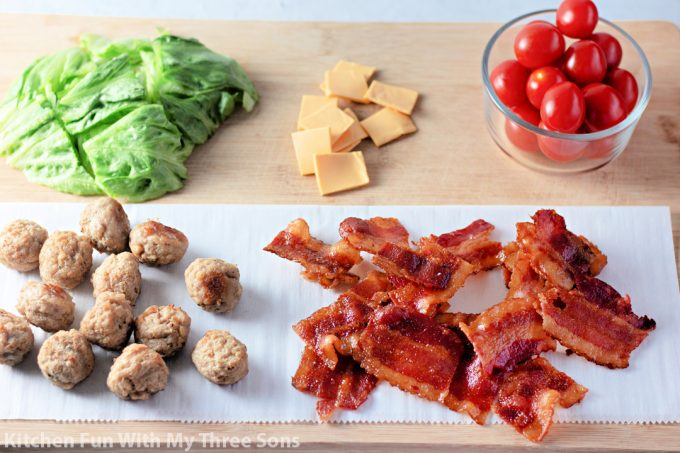 ingredients laid out on a cutting board to make the cheeseburger bites